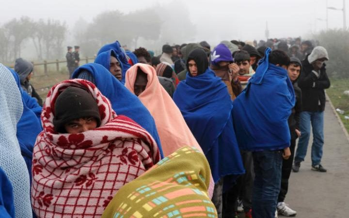 Migrants queue on the third day of their evacuation and transfer to reception centers in France, as part of the dismantlement of the Jungle camp