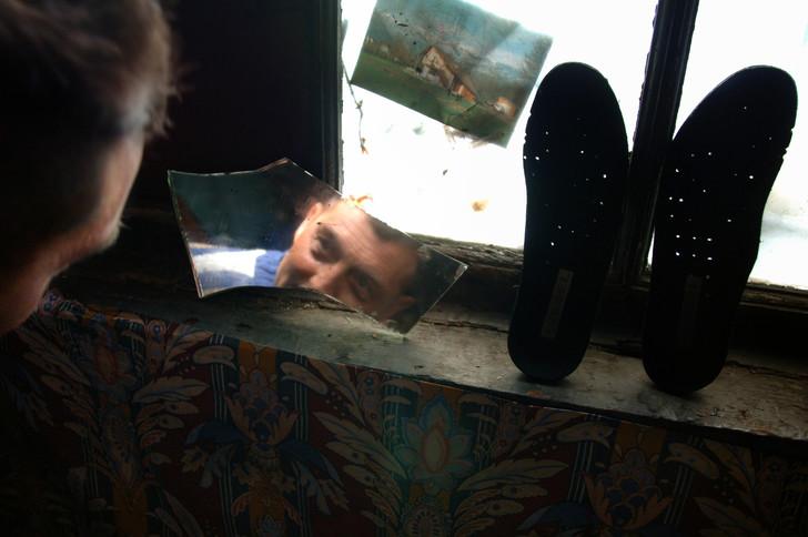 Un demandeur d'asile se regarde dans un morceau de miroir dans son abri de fortune, en banlieue lyonnaise.