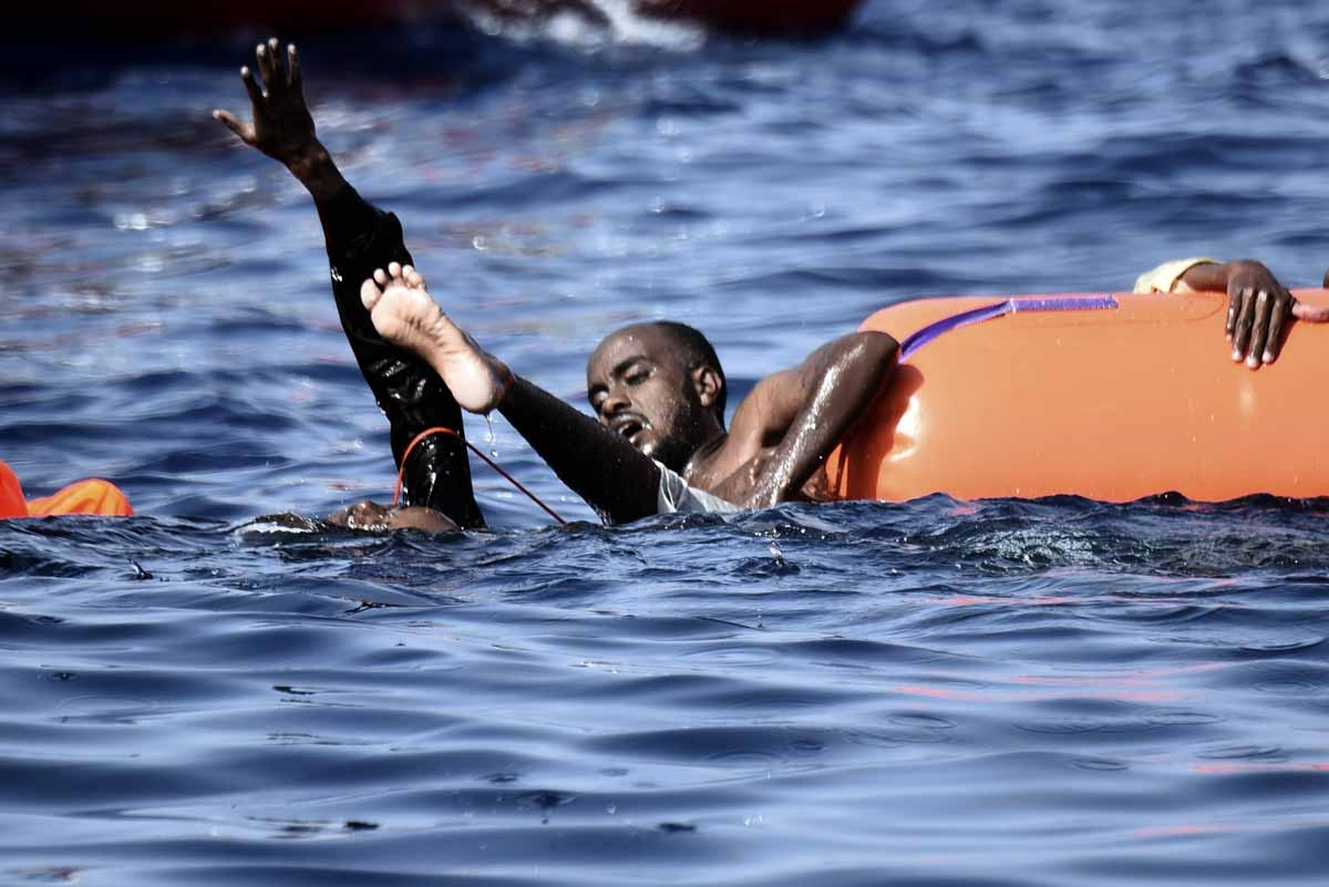 Migrants hold on a flotation tube as they wait to be rescued by members of Proactiva Open Arms NGO in the Mediterranean sea, some 12 nautical miles north of Libya, on October 4, 2016.