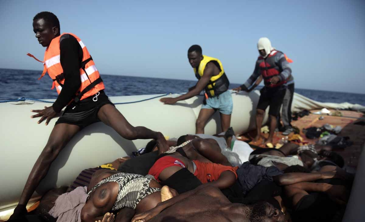 Migrants step over dead bodies while being rescued by members of Proactiva Open Arms NGO in the Mediterranean Sea, some 12 nautical miles north of Libya, on October 4, 2016.