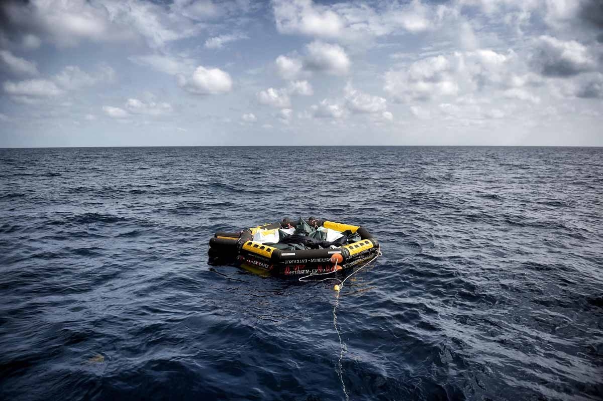 A life boat carrying the bodies of 29 refugees and migrants, who died on a rubber boat north of Libya while crossing the Mediterranean Sea, is dragged by a sailing boat of the Spanish NGO Proactiva Open Arms on October 5, 2016.