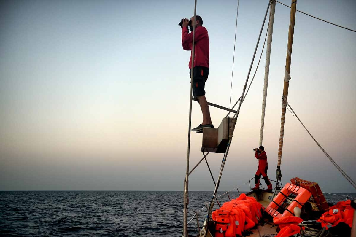 Member of Spanish humanitarian NGO Proactiva Open Arms, Savas Kourepinis (L) and Guillermo Canardo use binoculars to look for boats carrying refugees and migrants as they stand on the sailing boat Astral off the coast Libya on October 12, 2016.